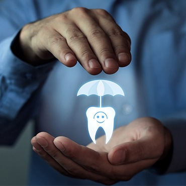 Hand holding animated tooth under an umbrella