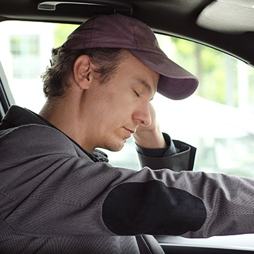 Tired man nodding off in car