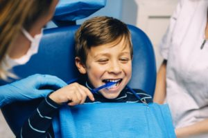 kid brushing teeth at dentist
