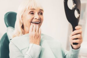 Woman smiling into mirror admires her new dental implants