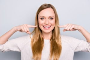 Woman smiling while pointing to her teeth after cosmetic bonding